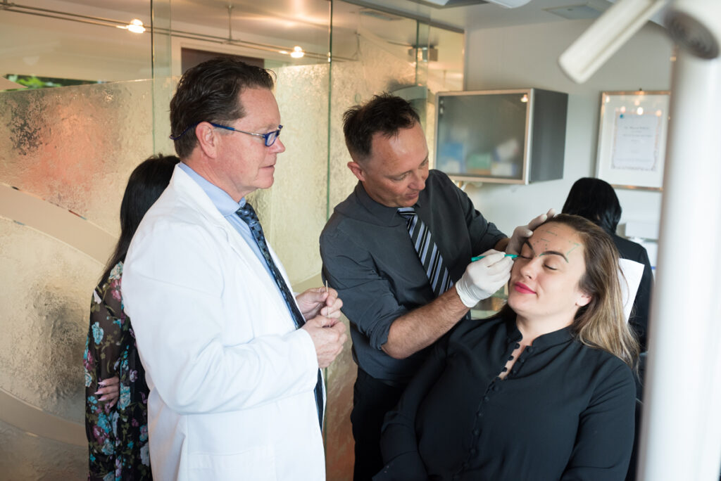 Doctor learning how to mark a patient for botox treatment.