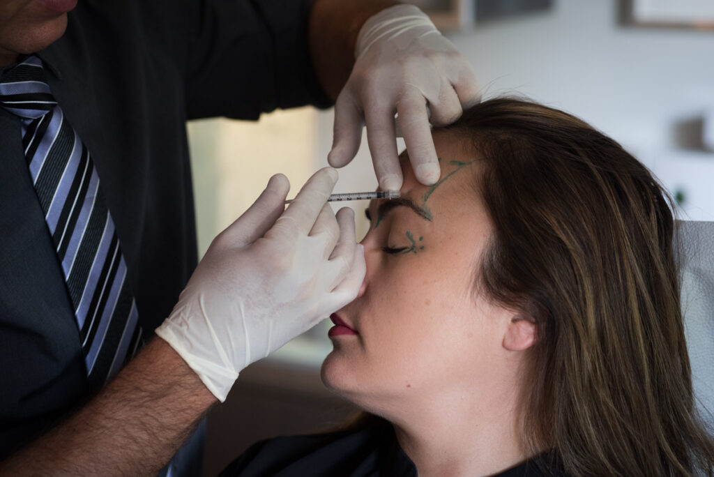Doctor injecting woman's forehead with botox using the PTIFA Injection Technique.