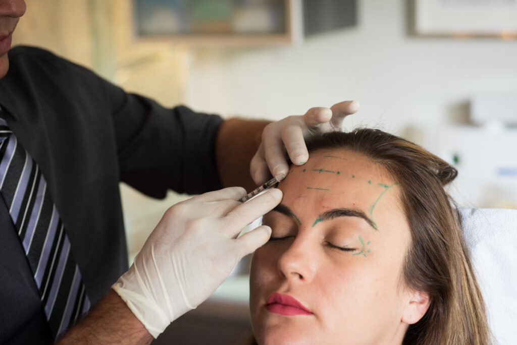 Woman getting botox in the frontalis (forehead) using the PTIFA Injection Technique.